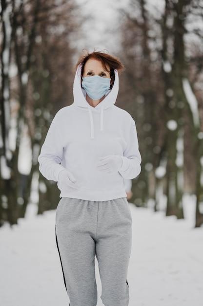 Colpo medio donna con maschera in esecuzione Foto Gratuite