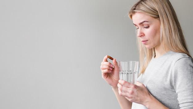 Medium shot woman with pill Free Photo