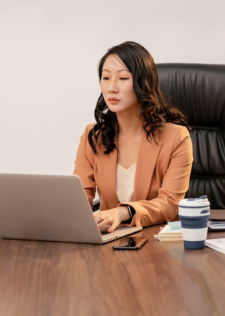ノートパソコンで作業中のミディアムショットの女性 無料写真