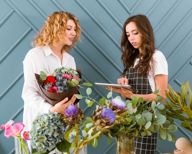 Medium shot women with bouquet and tablet Free Photo
