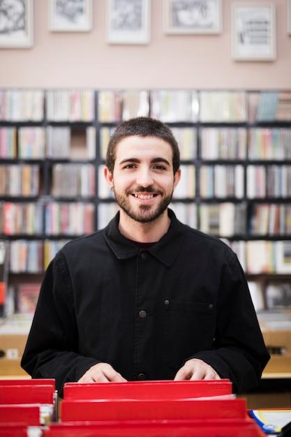 Medium shot of young man looking at camera in vinyl store Free Photo