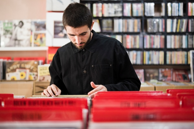 Medium shot of young man looking for vinyls in store Free Photo