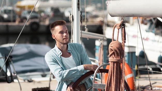 Молодой человек среднего кадра на лодке Premium Фотографии