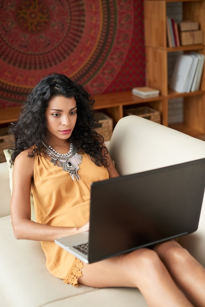 Medium shot of young woman working on laptop at home Free Photo