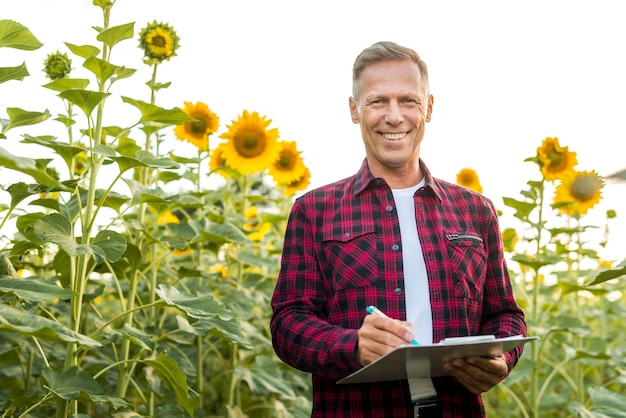 Medium view man with a clipboard in a field Free Photo