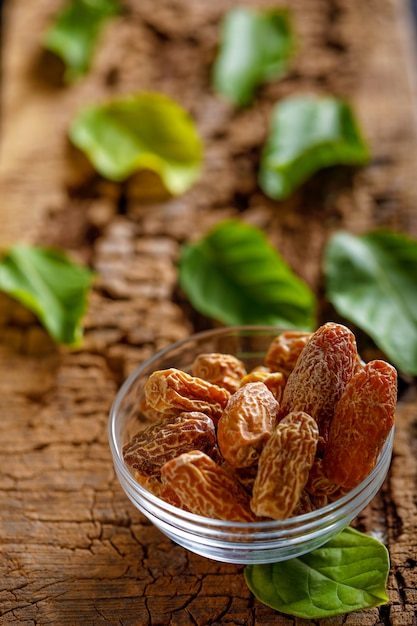 ボウルに乾燥日程。乾燥生有機medjool日付フルーツと古い木製のテーブルの上にボウルにグリーンミントをクローズアップ。 Premium写真