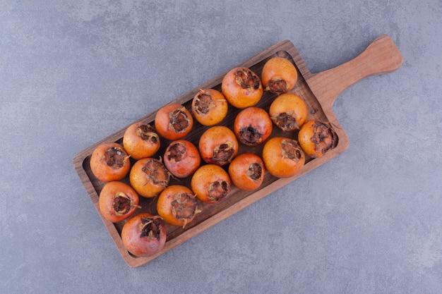 Медлары на деревянном блюде на сером фоне. Бесплатные Фотографии