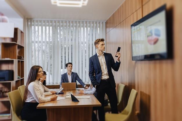 Встреча офисных работников за столом, просмотр презентации с диаграммами по телевизору Бесплатные Фотографии