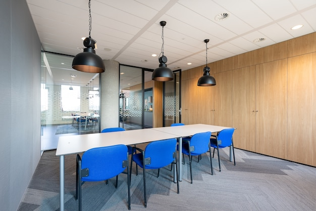 Interno della sala riunioni di un ufficio moderno con un lungo tavolo e sedie in legno intorno ad esso Foto Gratuite