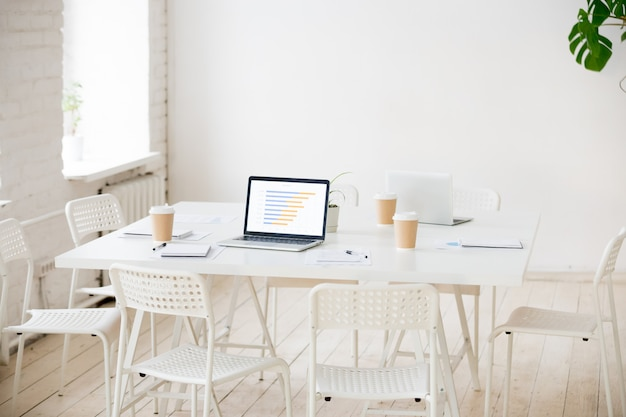 Meeting table with laptops and coffee in empty office room Free Photo