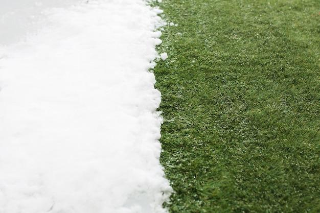 Встреча белого снега и зеленой травы крупным планом - между зимой и весной концепции фон. концептуальный образ о весне. Бесплатные Фотографии