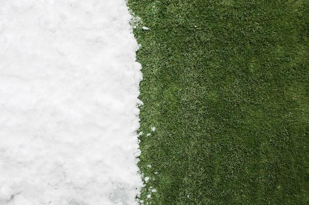 白い雪と緑の草に出会うクローズアップ。冬と春のコンセプトの背景の間。 無料写真