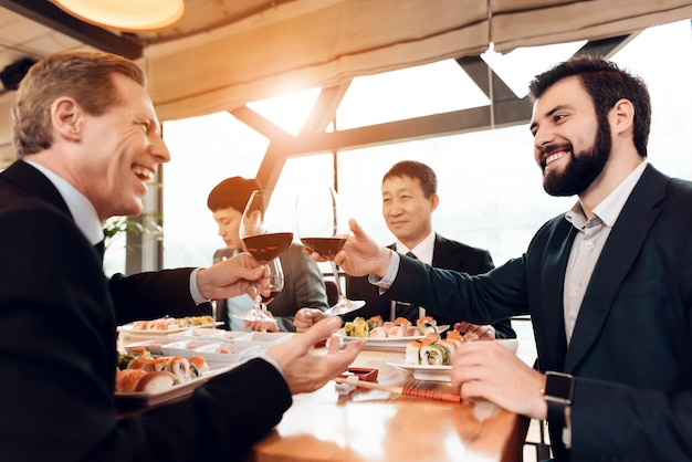 Meeting with chinese businessmen in suits in restaurant. Premium Photo