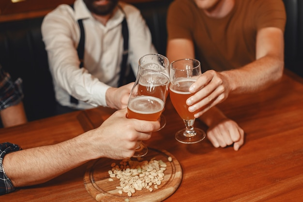 親友との出会い。カジュアルな服装で3人の幸せな若い男性が一緒にバーに座って話したり、ビールを飲んだりします。 無料写真