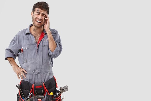 Melancholic handyman posing against the white wall Free Photo