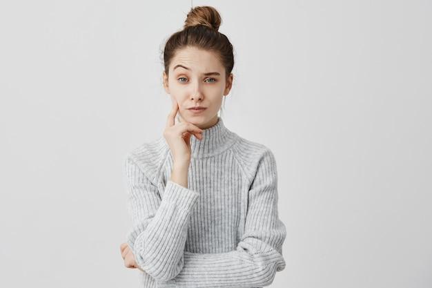 陰気な表情で立っている憂鬱な20代の少女が指で頬を触る。片方の眉を反射して見上げる眉をひそめている女性のコピーライター。パズル 無料写真