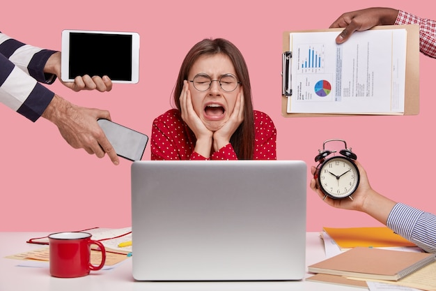 憂鬱な、働くコンセプト。落ち込んでいる悲しい女性は絶望して泣き、ムーを開いたままにし、丸い眼鏡をかけ、多くの仕事をし、試験の準備をします 無料写真
