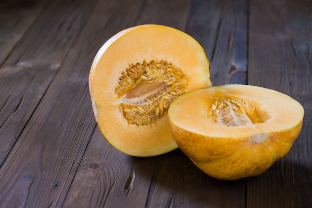 Melon cut in half on a wooden surface Premium Photo