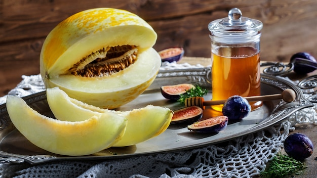Melon with honey,  figs, on a rustic wooden table Premium Photo