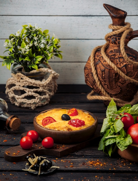 Melted cheese topped with tomato slices and olive in pottery pan Free Photo