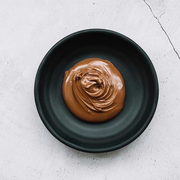 Melted chocolate in black bowl over the white backdrop Free Photo