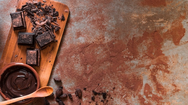 Melted chocolate bowl and crushed bar on chopping board with wooden spoon Free Photo