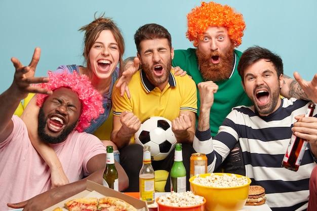 男性と女性のファンは、自宅のテレビでサッカーを観戦し、エキサイティングなゲームを楽しみ、拳を握り締め、勝利を祝い、前向きな感情を表現し、ボウルにポップコーンを入れ、ピザを食べ、青い壁でポーズをとります。 無料写真