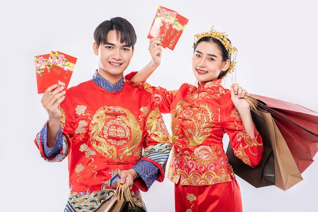 男性と女性は赤い封筒で買い物に行くために紙袋を運びます 無料写真