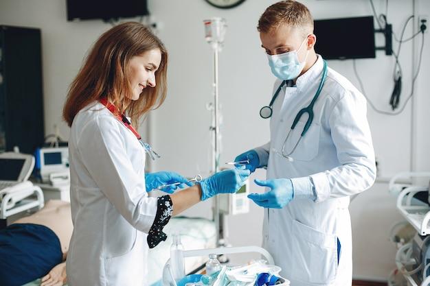 Мужчины и женщины в больничных халатах держат в руках медицинское оборудование. медсестра набирает лекарство в укол. Бесплатные Фотографии