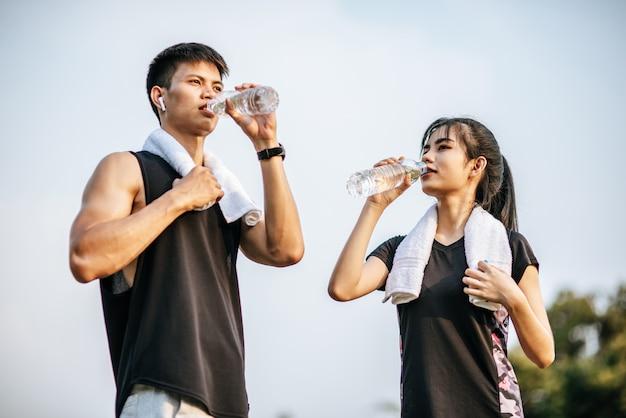 男性と女性は運動後に水を飲むために立っています。 無料写真