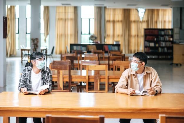 マスクをかぶった男女が図書館に座って読んでいます。 無料写真