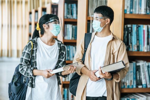 マスクをした男性と女性が立ち、図書館で読書をします。 無料写真