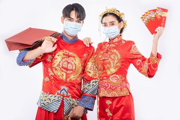 チャイナドレスとマスクを身に着けている男性と女性赤い封筒で買い物をするために紙袋を運ぶ 無料写真