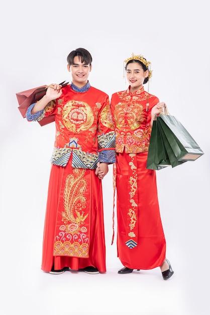 チャイナドレスを着た男女が紙袋を持って買い物に行きます。 無料写真