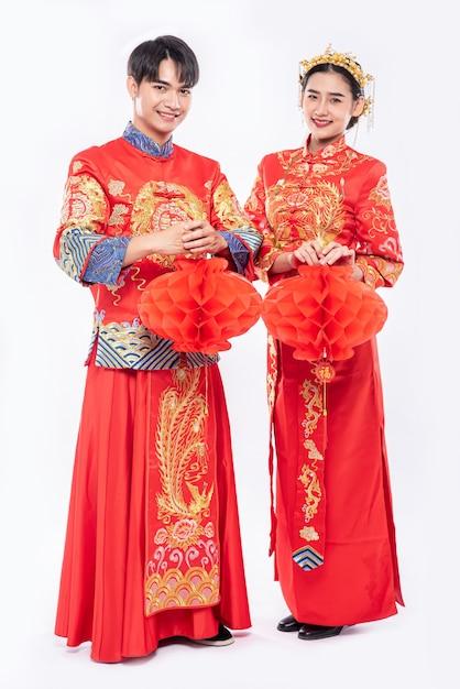 남자와 여자는 흰색 배경에 고립 벌집 램프와 Qipao 서 입고. 무료 사진