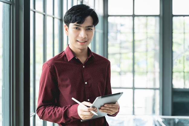 Men are smiling and cheerful. using the tablet and holding it on hand. he use tablet to work, c Premium Photo