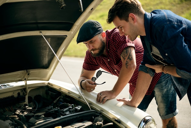 Men checking broke down car on street side with open hood Premium Photo