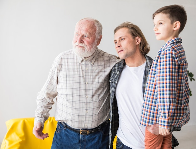 Men of different generations standing and looking away Premium Photo
