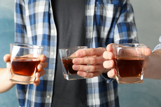 Men drink, cheers. glasses of whiskey against blue Premium Photo