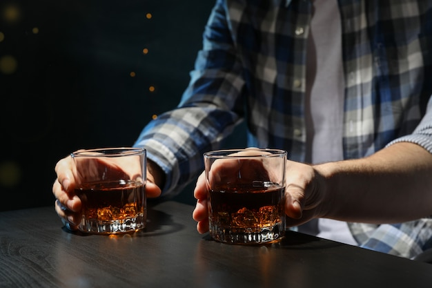 Men drink whiskey at the bar, close up. blurred lights men drink whiskey at the bar, close up. blurred lights Premium Photo