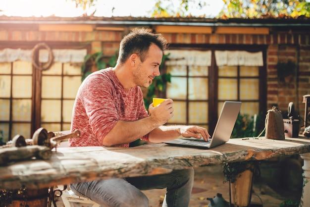 Men drinking coffee and using laptop at backyard patio Premium Photo
