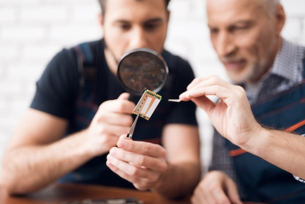 Men examine pc component with magnifying glass. Premium Photo