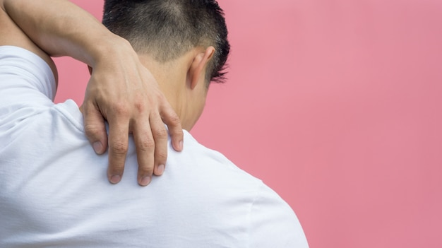 Men feeling pain in his shoulder on a pink background. Premium Photo