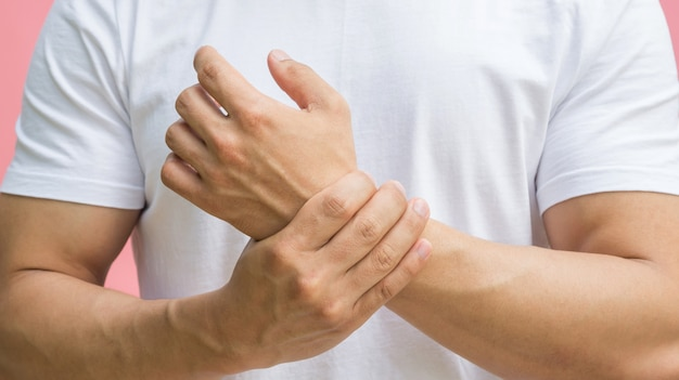 Men feeling pain in his wrist on a pink background. Premium Photo