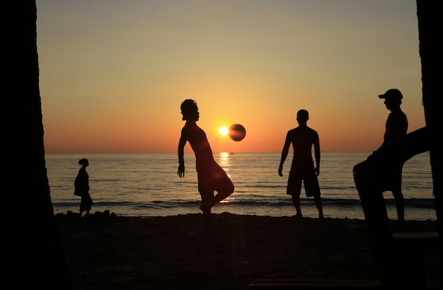 The men footballs team, rehearsals playing football at the beach of the sea with sunset. Premium Photo