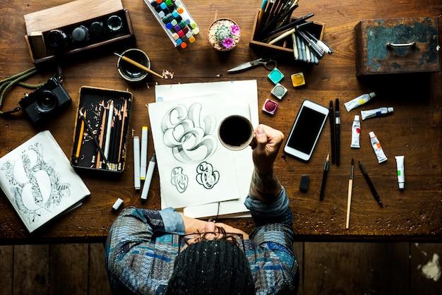 Мужчины хипстер, держащий кофе и иллюстрации на столе Premium Фотографии