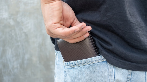 Men hold a brown wallet from a jeans pocket. Premium Photo