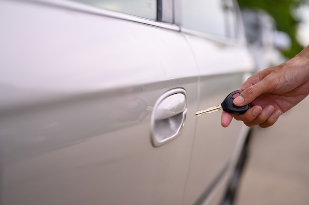 Men hold the car keys to open the car. Premium Photo