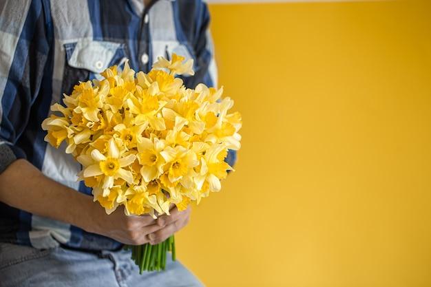 水仙の大きな花束を持っている男性。 無料写真