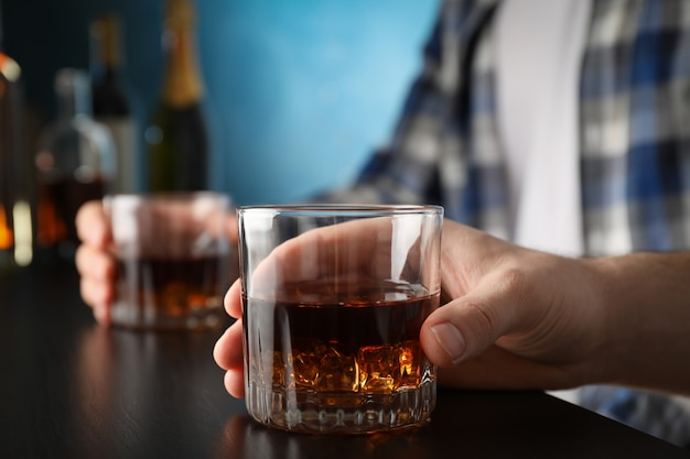 Men holding glasses of whiskey at the bar, space for text Premium Photo